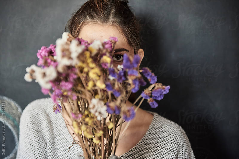 Young woman behind the bunch of flowers  by Guille Faingold for Stocksy United