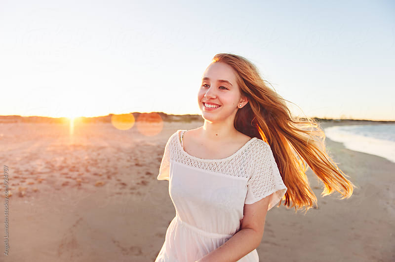 Smiling teenage girl at the beach at sunset by Angela Lumsden for Stocksy United