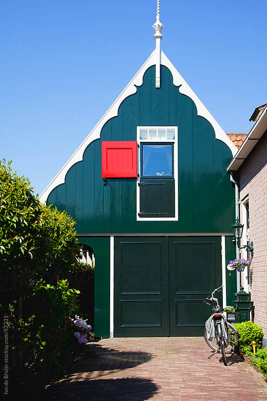 A classic green wooden house in the Netherlands with a red hatch, white ornaments and a bike on the  by Ivo de Bruijn for Stocksy United