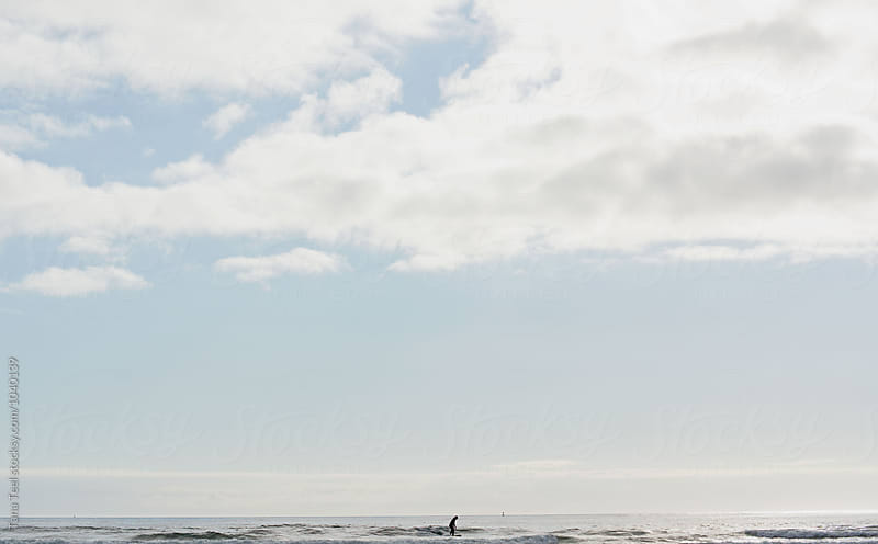 surfer riding waves in background of pacific ocean  by Tana Teel for Stocksy United