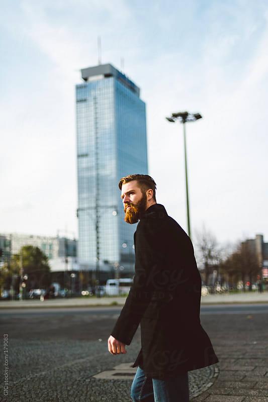 Man with long beard walking in Berlin by GIC for Stocksy United