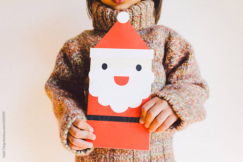 A boy holding big Santa Claus card by Nabi Tang for Stocksy United