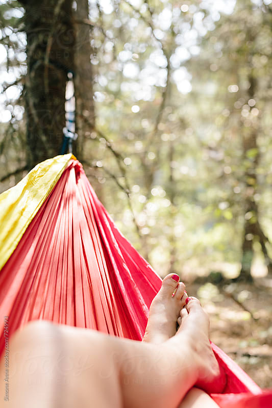 Woman's feet and legs in hammock by Simone Anne for Stocksy United