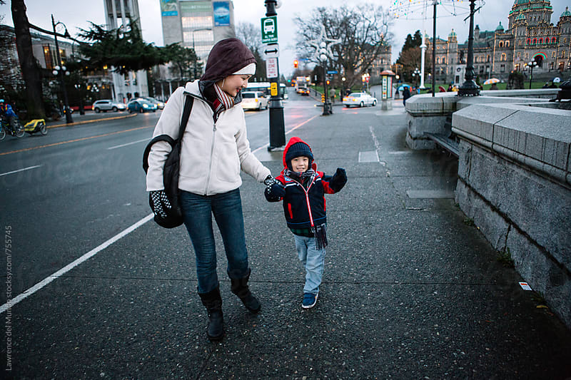 A mother and her son enjoy each other's company while walking on the street. by Lawrence del Mundo for Stocksy United