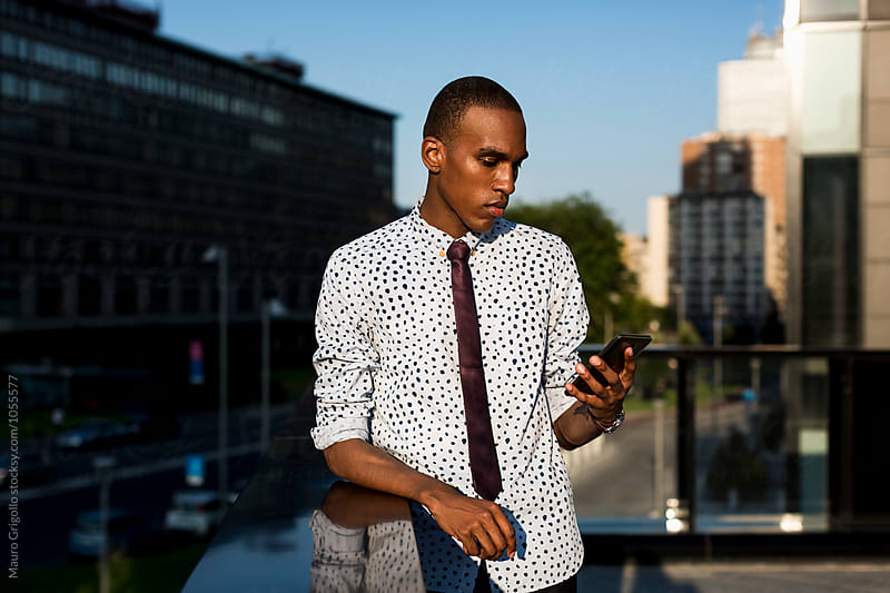 Stylish African American Businessman using mobile phone outdoor  by Mauro Grigollo for Stocksy United