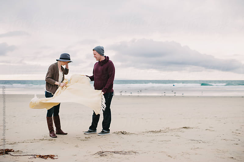 Couple on date on windy beach with blanket by Kristin Rogers Photography for Stocksy United