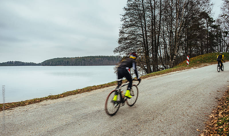 Cyclists passing a lake. Its late autumn. by Tõnu Tunnel for Stocksy United