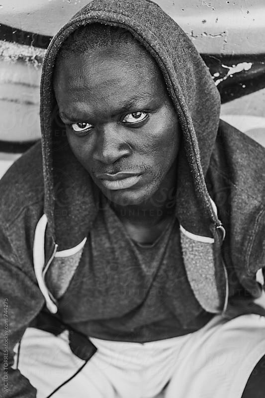 Portrait of a Serious Black Man with Hood by Victor Torres for Stocksy United