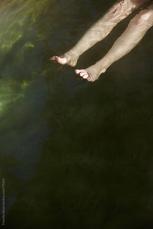 Woman's legs floating on water at hot springs by Trinette Reed for Stocksy United