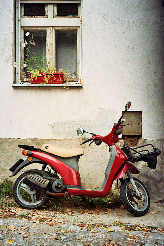 red retro vespa in the street by Sonja Lekovic for Stocksy United