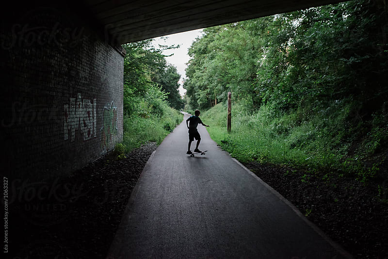 Boy skateboarding under bridge by Léa Jones for Stocksy United