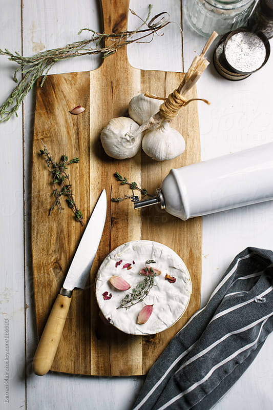 Ingredients for baked camembert cheese on a wooden cutting board. Seen from above. by Darren Muir for Stocksy United