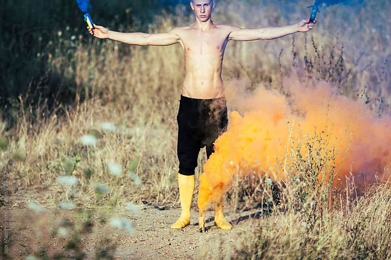 young boy in yellow stockings holding colorful smoke bombs in nature by Igor Madjinca for Stocksy United