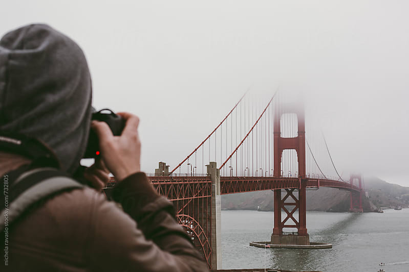 Man photographing Golden Gate Bridge in the fog by michela ravasio for Stocksy United