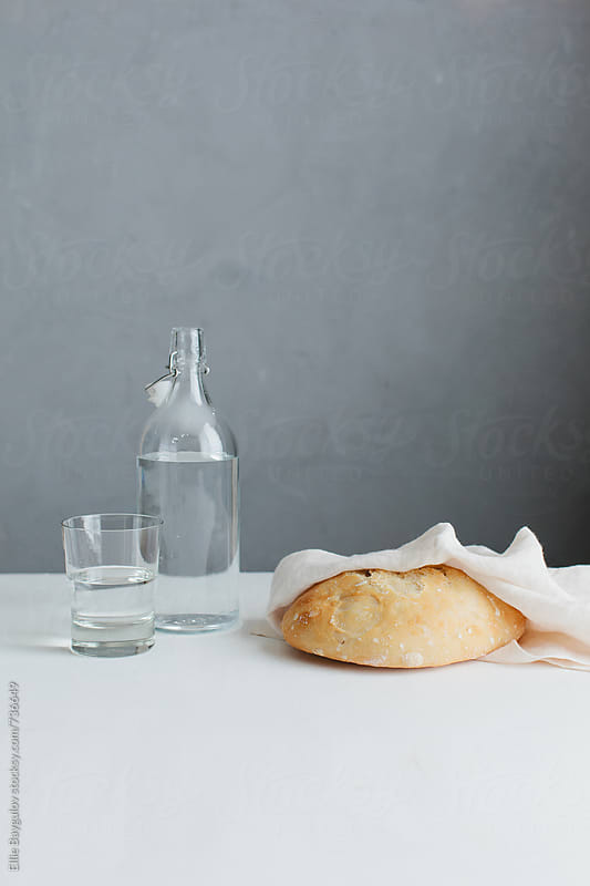 Freshly baked bread with water by Ellie Baygulov for Stocksy United