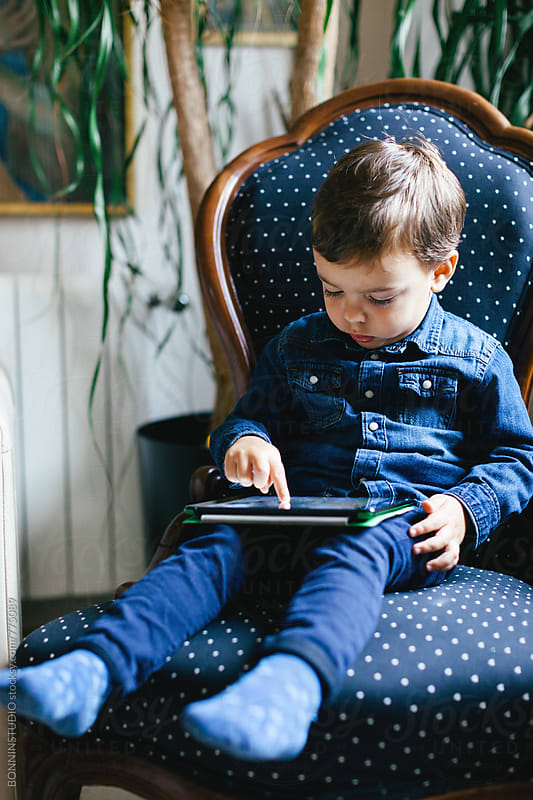Child using a digital tablet at home. by BONNINSTUDIO for Stocksy United