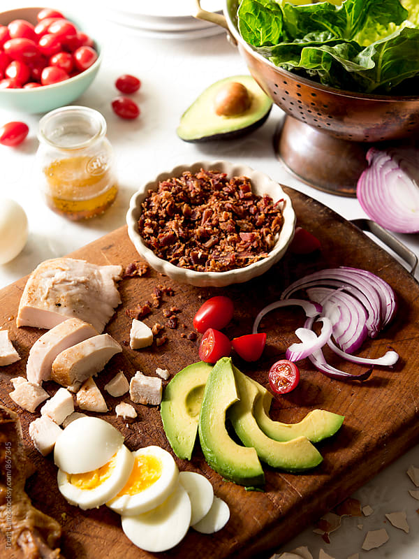 Close-up of delicious cobb salad ingredients on wooden board by Trent Lanz for Stocksy United