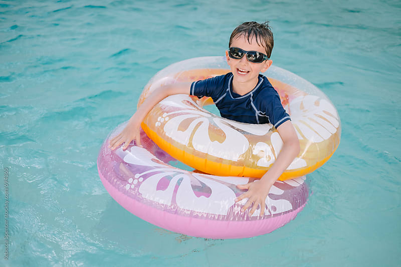 Smiling child floats in the swimming pool by Rebecca Spencer for Stocksy United
