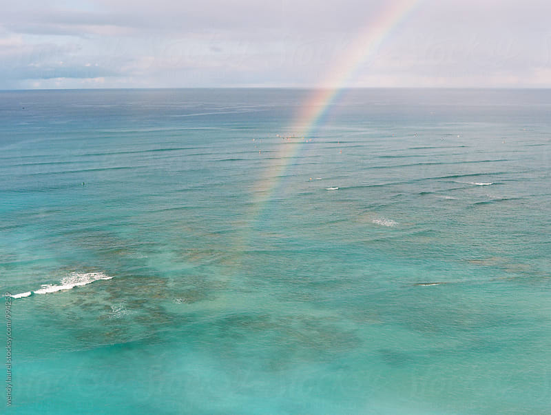 rainbow in ocean at waikiki beach with blue water by wendy laurel for Stocksy United