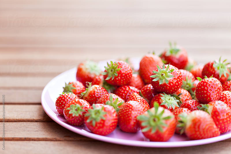 fresh strawberries on a plate on wooden background by Corinna Gissemann for Stocksy United
