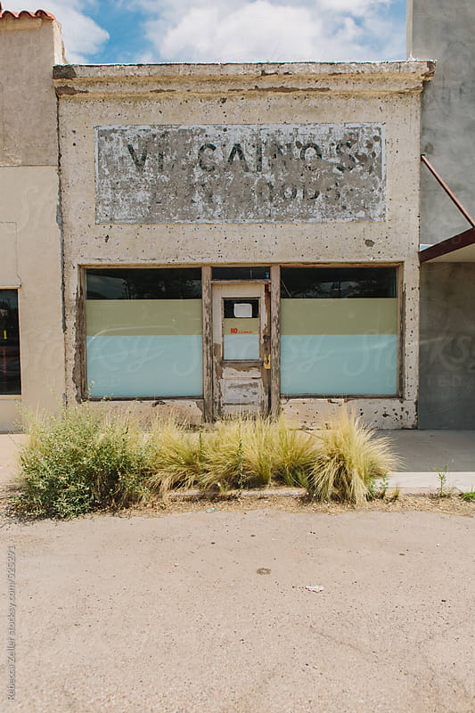 an old, run-down store front in a town in west texas by Rebecca Zeller for Stocksy United