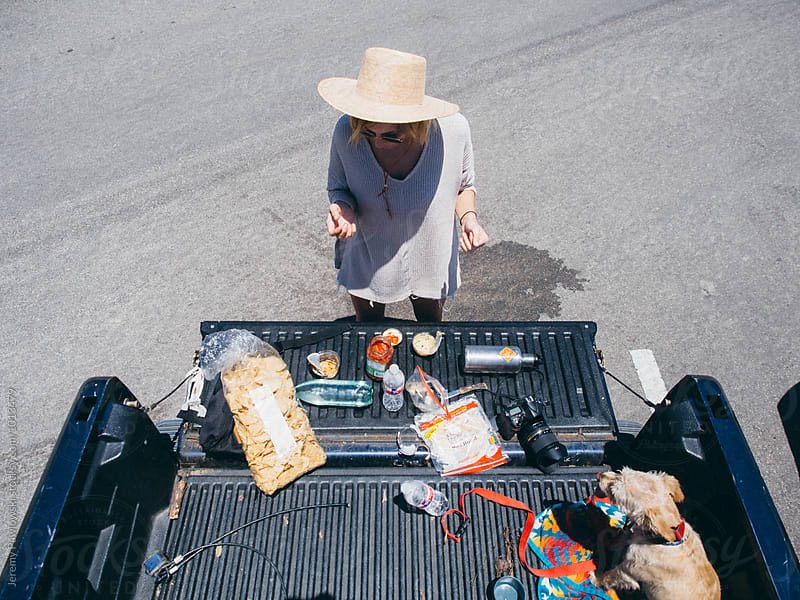 Girl in straw hat making lunch on truck tailgate by Jeremy Pawlowski for Stocksy United