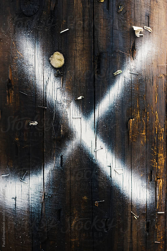 X spray painted onto telephone pole, close up by Paul Edmondson for Stocksy United