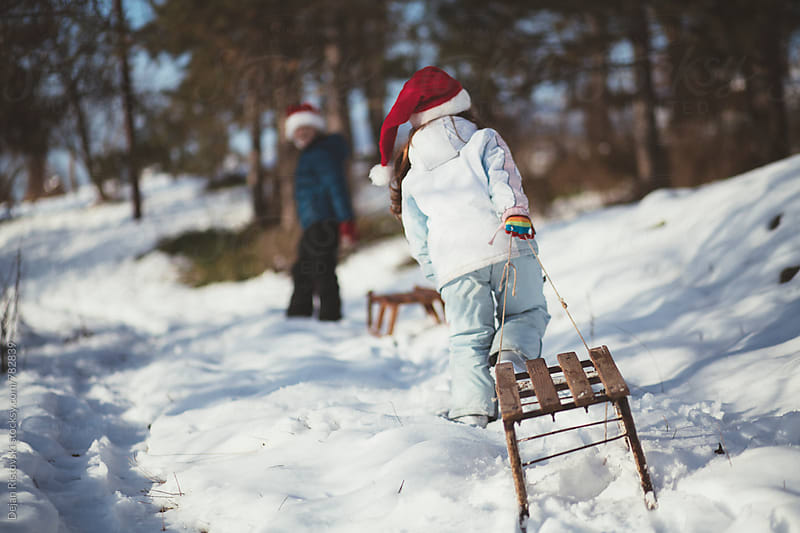 Children sledging in forest. by Dejan Ristovski for Stocksy United