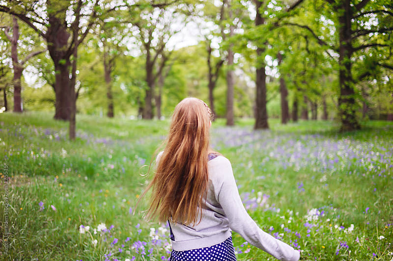 Girl running through field of bluebells by Angela Lumsden for Stocksy United