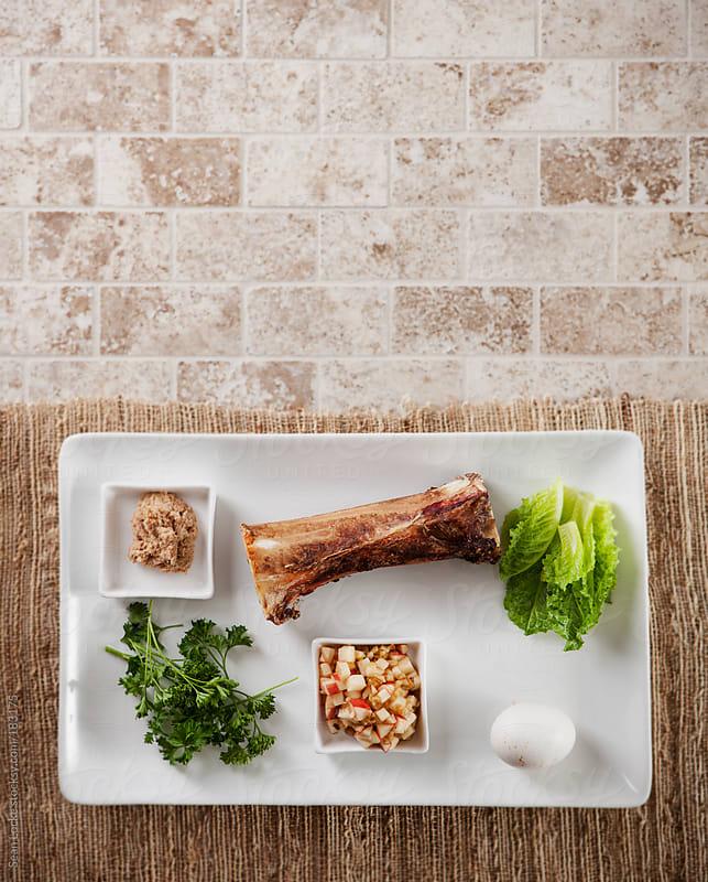Passover: Seder Plate On Straw Runner On Tile by Sean Locke for Stocksy United