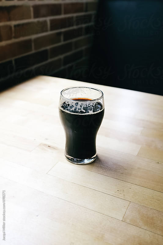 Half a pint of stout on a table by Jacqui Miller for Stocksy United
