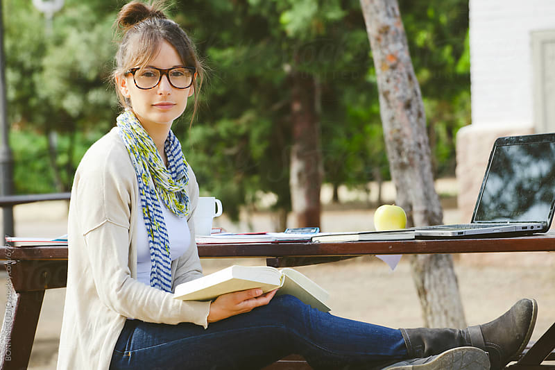 Young student woman with glasses wearing casual clothes and reading on a park. by BONNINSTUDIO for Stocksy United