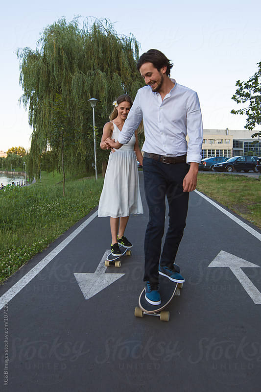 Couple having fun on skateboards outdoor by RG&B Images for Stocksy United