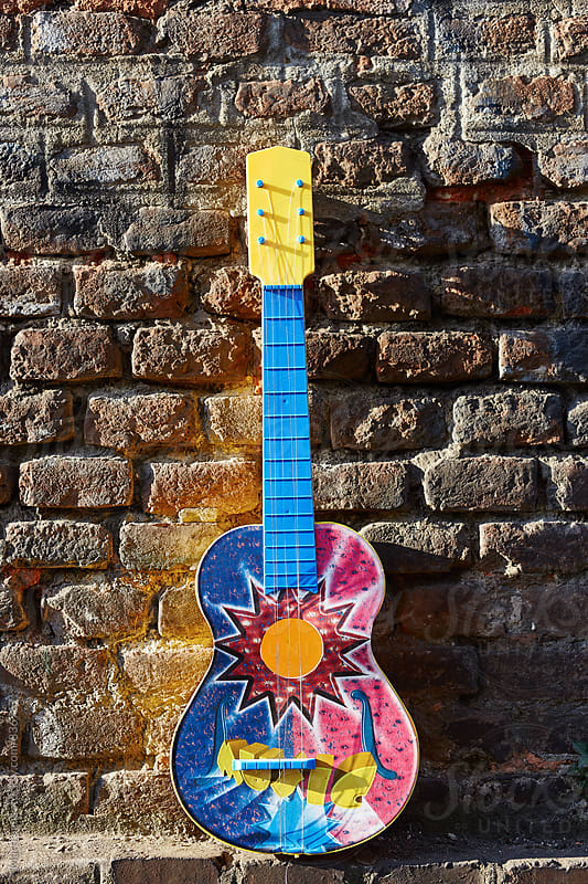 Colorful guitar against of grunge brick wall by Martí Sans for Stocksy United