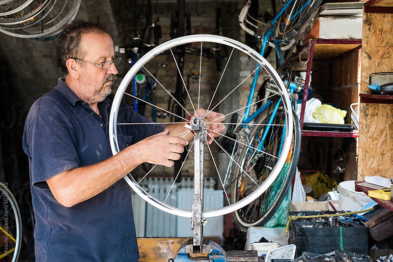 Senior Man Repairs a Bike Wheel in a Garage  by Mosuno for Stocksy United
