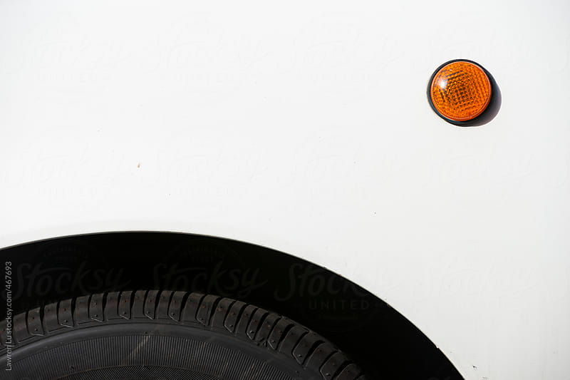 Close up of the front side panel and wheel arch of a white car by Lawren Lu for Stocksy United