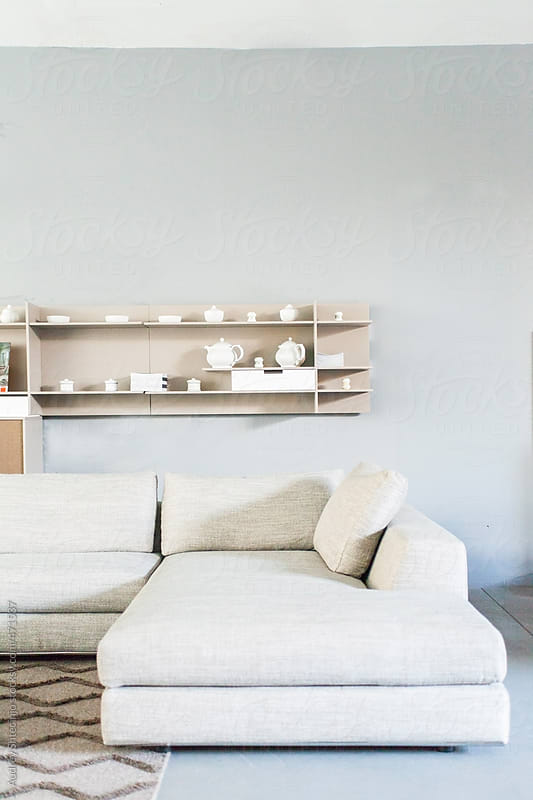 Minimalistic living room with gray wall.  by Audrey Shtecinjo for Stocksy United