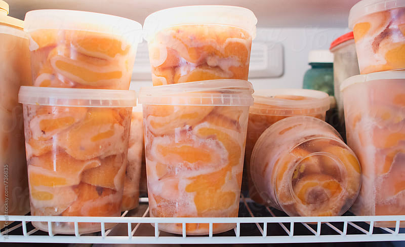 Homegrown peaches frozen in recycled containers by Tana Teel for Stocksy United