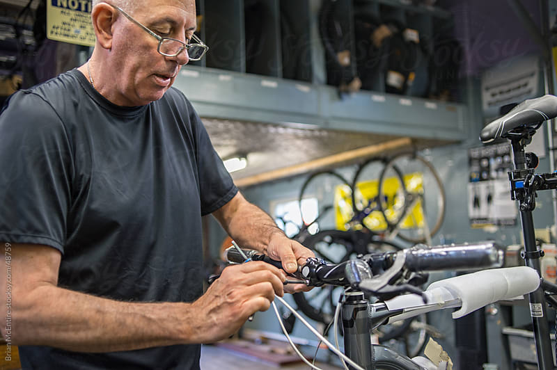 Local Bike Shop: Store Owner Assembles New Bicycle by Brian McEntire for Stocksy United