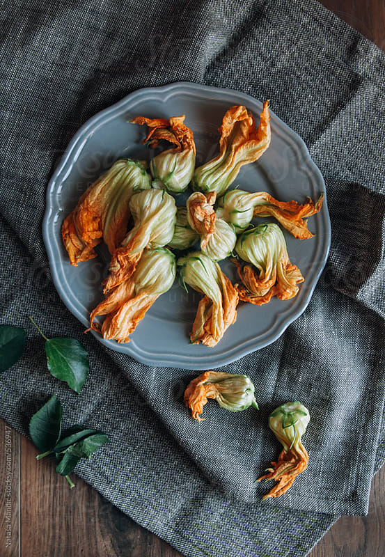 Courgette flowers on a plate by Nataša Mandić for Stocksy United