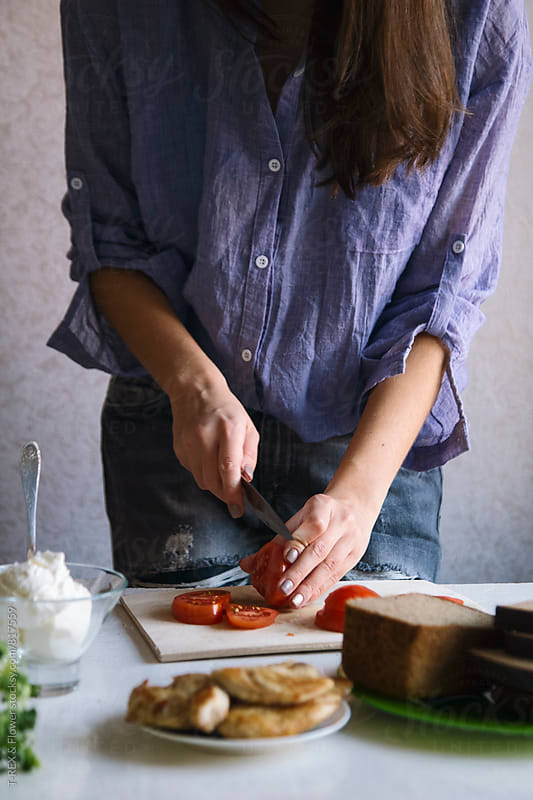 Woman cutting tomatoes with knife. Unrecognizable. by T-REX & Flower for Stocksy United