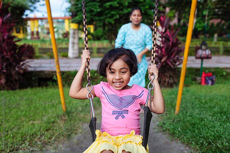 Little girl enjoying the swing in a park by Saptak Ganguly for Stocksy United