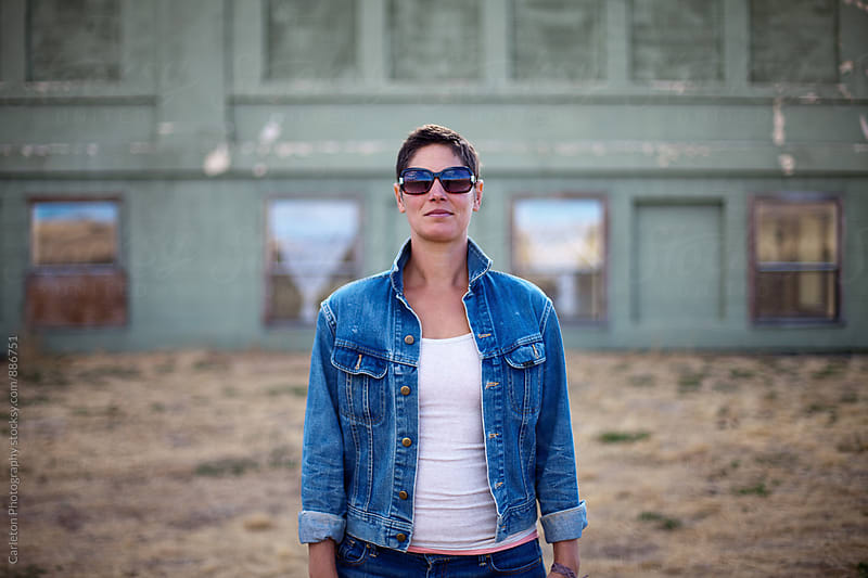 Woman with short hair rocks a denim jacket and sunglasses by Carleton Photography for Stocksy United