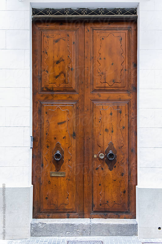 Wooden door  in a white wall by Marilar Irastorza for Stocksy United