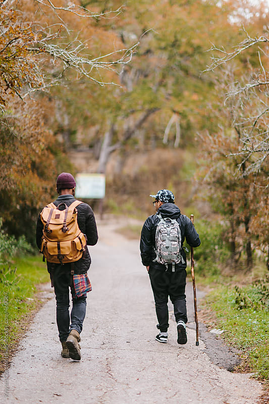 Two male explorers outside enjoying nature on a cold rainy day.  by Kristen Curette Hines for Stocksy United