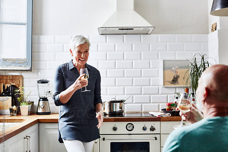 Senior Couple Enjoying Wine In Kitchen by ALTO IMAGES for Stocksy United
