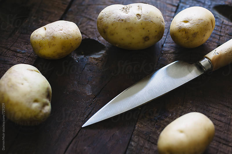 Potato's and a knife on a wooden table. by Darren Muir for Stocksy United