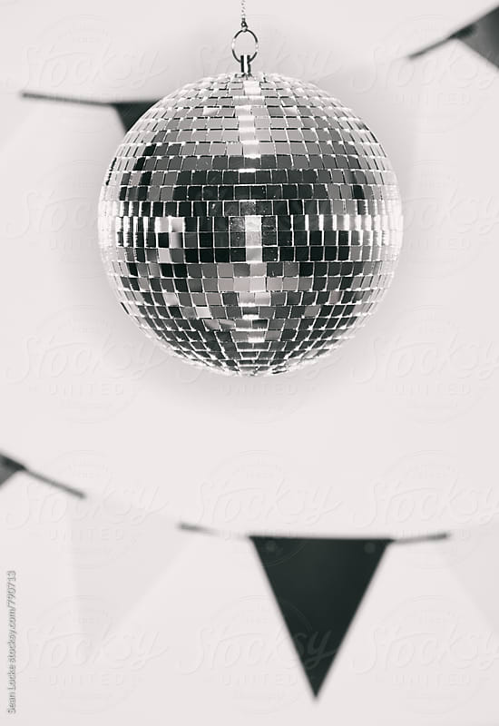 NYE: Mirrored Ball Hangs In Front Of Party Banners by Sean Locke for Stocksy United