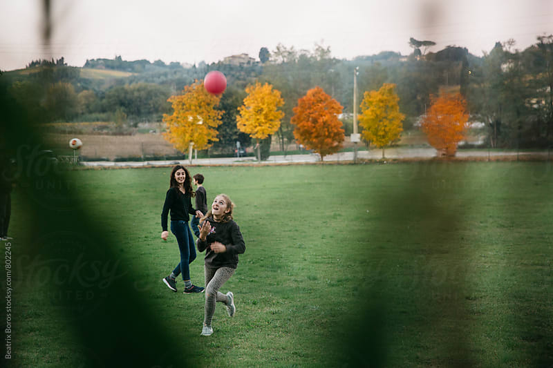 Kids playing with ball at twilight on a field in Autumn by Beatrix Boros for Stocksy United