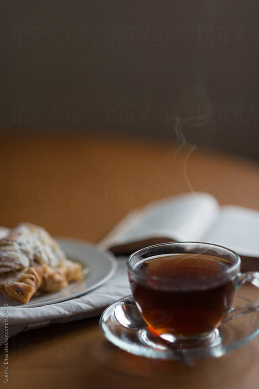 A glass cup of tea with a fresh almond croissant and a book by Gabriel Diaz for Stocksy United